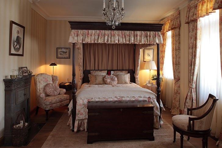 Пример правильно подобранной мебели для спальни в английском стиле. Кровать с балдахином оформлена в строгом соответствии стилю.