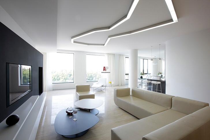 Пример правильного подбора освещения для гостиной в стиле минимализм. В соответствии с требованиями стиля в создании интерьера используются геометрические формы и строгие линии.