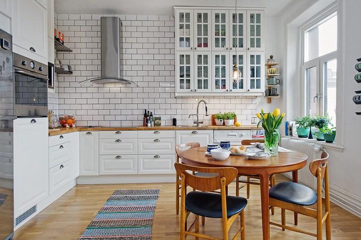 Интерьер кухни выполнен в скандинавском стиле, который выражен белой, спокойной гаммой оформления.