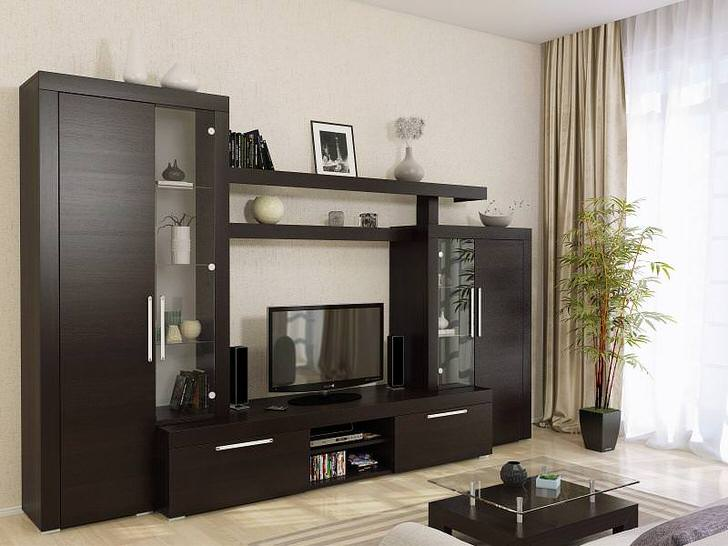 Меблировка гостиной подобрана в цвете венге. Сдержанное оформление с декоративными лаконичными деталями смотрится презентабельно.