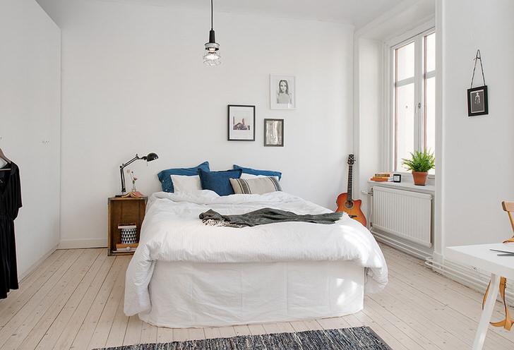 Спальня в скандинавском стиле обязательно должна быть светлой. Белая отделка стен и потолка, светло-бежевый паркет, не завешенные окна делают жилое пространство просторным.