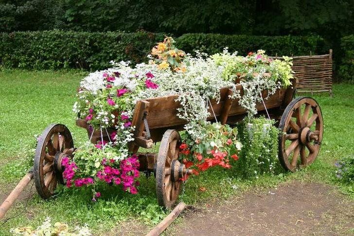 В качестве утвари для создания клумбы использовалась старая, реставрированная телега. Интересное решение для декора двора загородного дома.
