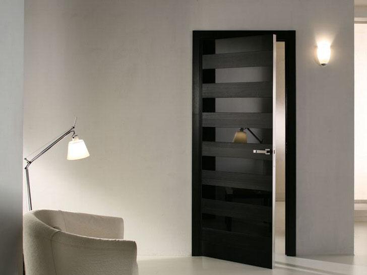 Интересным дизайнерским решением становится чередование матовых и глянцевых поверхностей. Межкомнатные двери использовались для оформления интерьера гостиной в стиле модерн.