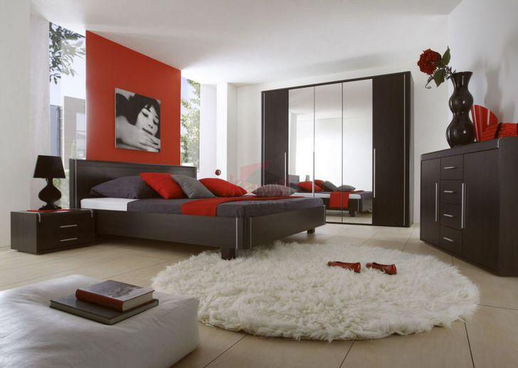 Деревянная мебель венге в современном исполнении гармонично сочетается с ковром с высоким ворсом и другими декоративными деталями ярко-красного цвета.