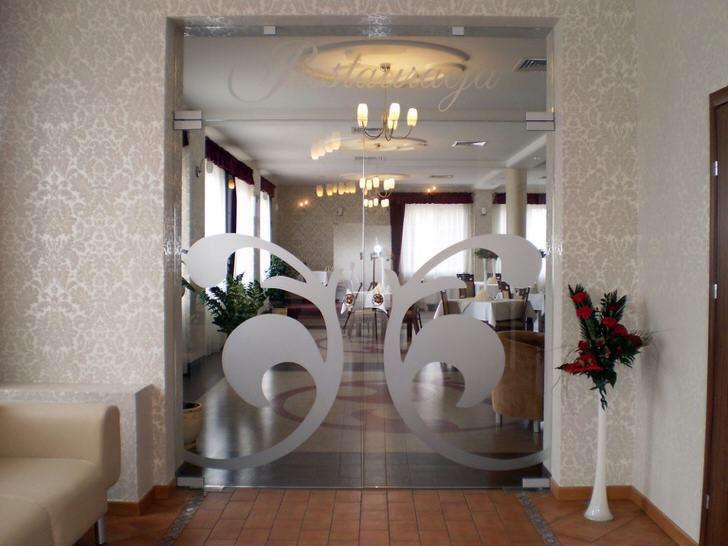 Стеклянные двери в стиле модерн украшены серебристым симметричным витиеватым узором. Оригинальная деталь для современного интерьера.
