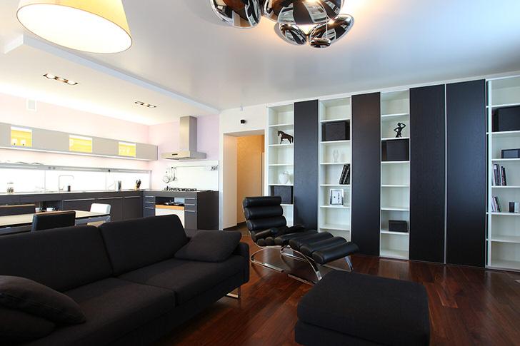 Черный диван, состоящий из подушек, и небольшой пуфик созданы под заказ для оформления интерьера в стиле хай тек.