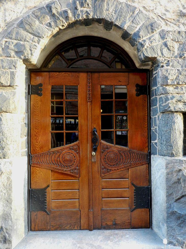 Двери в стиле модерн украшают парадный вход загородного коттеджа с фасадом из натурального камня.