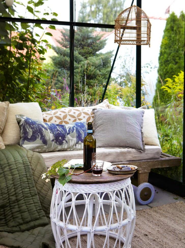 Лучшим декором беседки в скандинавском стиле считается диван с большим количеством мягких подушек.