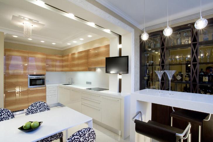 Дизайнерский проект, составленный для кухни в стиле модерн, предусматривает оснащение комнаты зонированным освещением. Потолочные люстры органично объединены с точечным светодиодным освещением.