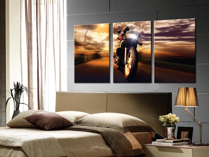 Спальня молодого холостяка декорирована с помощью модульной картины, на которой изображен мотоциклист.