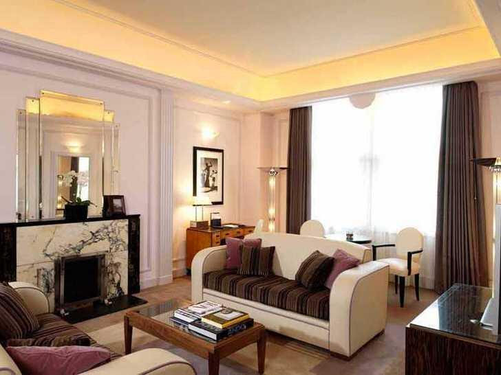 Отличный пример того, что стиль арт деко может быть в меру сдержанным. Гламурный интерьер гостиной уютен по-семейному.