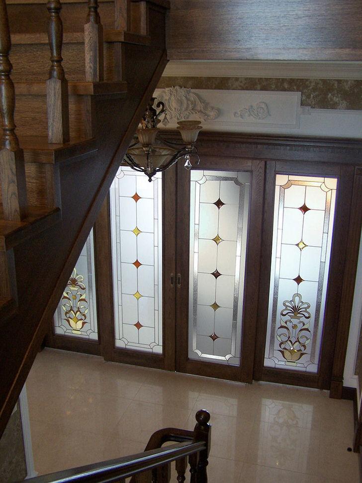 Двери со стеклянными вставками украшены матовой витражной пленкой с незамысловатым рисунком. Не вычурный, сдержанный дизайн дверей органично впишется в классический интерьер холла.