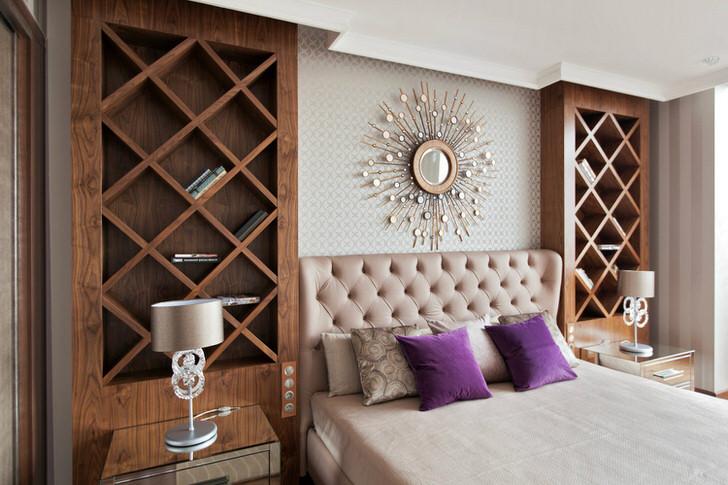 Мягкое изголовье шикарной двуспальной кровати выполнено из натурального, стеганного атласа. По бокам у кровати стоят высокие декоративные полки, куда хозяин жилья может складывать любимые книги.