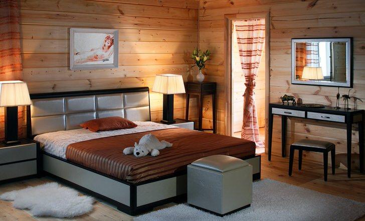 Стены комнаты из деревянного сруба гармонично сочетаются с мебелью для спальни цвета ценге.