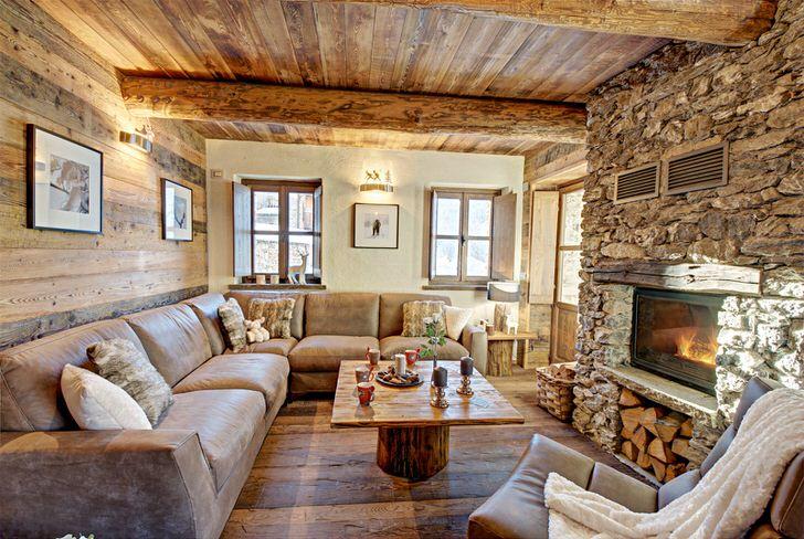 Электрический камин, имитирующий горение пламени, делает атмосферу в гостиной в стиле шале теплой и романтической.