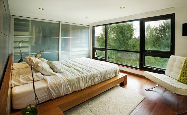 Низкая кровать из дерева гармонично вписывается в интерьер спальни в стиле модерн.