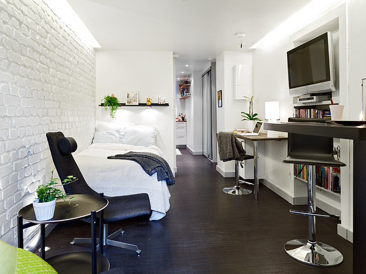 Примечательной деталью в интерьере становится стена из белого кирпича. Небольшая гостевая спальня оформлена в современной интерпретации скандинавского стиля.