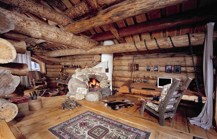 Множество деревянных отделочных материалов, мебель в деревенском стиле, камин - все, что нужно для оформления гостевой комнаты в стиле шале.