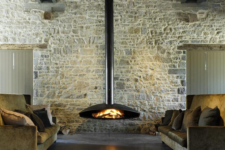 Подвесной камин может быть расположен вблизи стены или по центру комнаты. Все зависит от фантазии и предпочтений владельцев жилья.