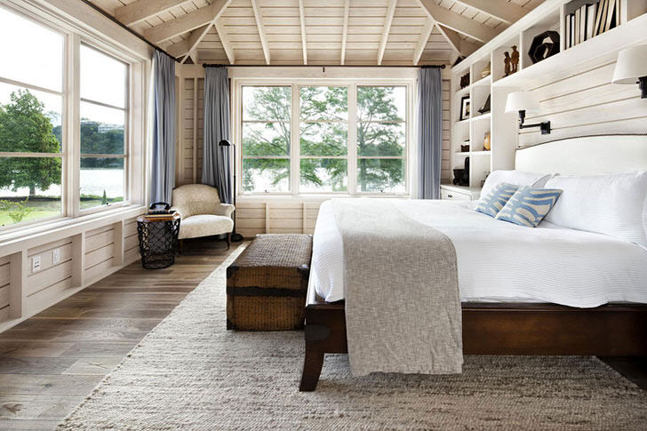 Спальня в скандинавском стиле с большой двуспальной кроватью из дерева в доме французского бизнесмена.