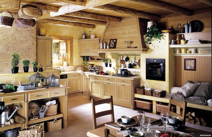 Кухонный гарнитур из светлого дерева гармонично вписывается в интерьер кухни в деревенском стиле. Множество полочек, навесных шкафов позволяют сэкономить полезное пространство в комнате.
