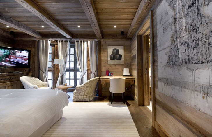 Мебель для гостиной в стиле шале выбирается преимущественно светлых оттенков. Интересным дизайнерским решением является меблировка комнаты мягкой мебелью.