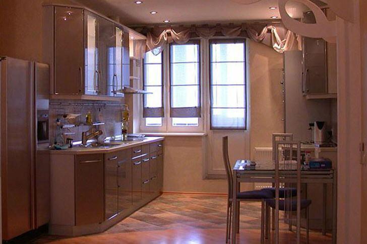 Вместительный кухонный гарнитур с навесными шкафами в светло-бежевых тонах смотрится привлекательно и изысканно. Вместо кладовой дизайнер сделал нишу, куда для удобства был помещен холодильник.