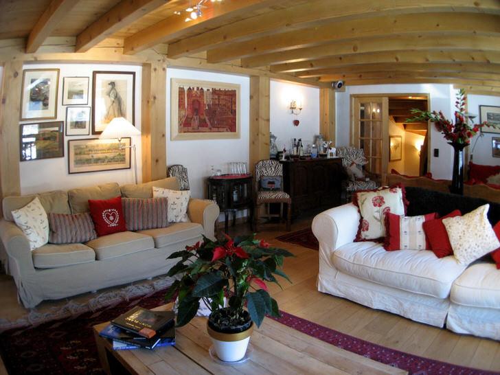 Мягкие, объемные диваны в гостиной в стиле шале декорированы разноцветными подушками.