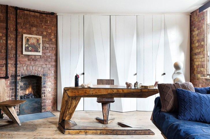 Гостиная с личным кабинетом украшена дровяным камином. Необычным декоративным элементом становятся вязанные подушки плед, которые делают стиль лофт теплым и уютным.