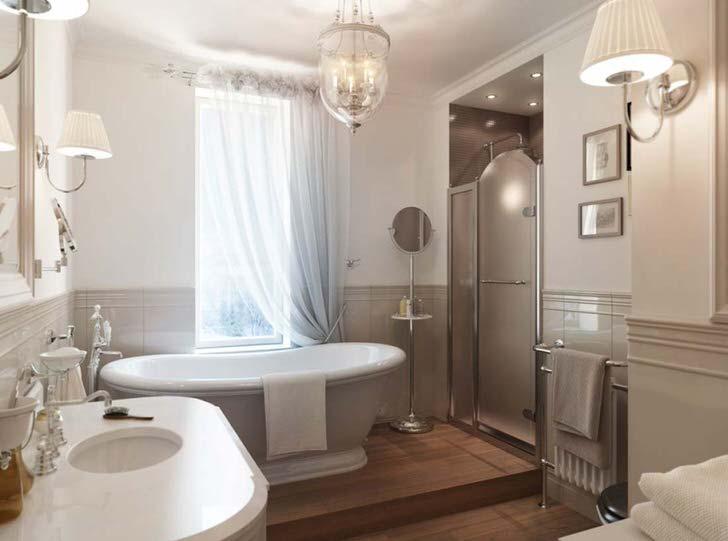 Большая керамическая белоснежная ванная становится изюминкой интерьера комнаты. Окно завешено полупрозрачной ниспадающей занавеской из натуральной ткани, что полностью соответствует стилю модерн.