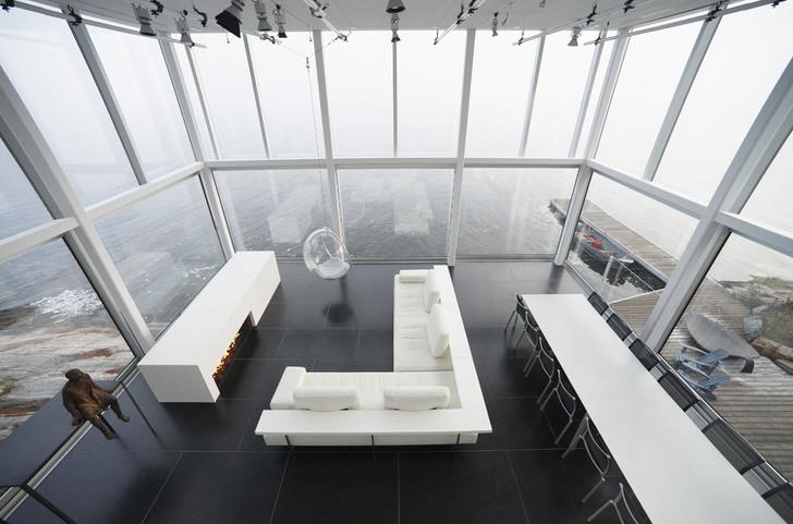 Лаконичный дизайн гостиной в стиле минимализм. Интересным элементом меблировки становится подвешенное к высокому потолку кресло.