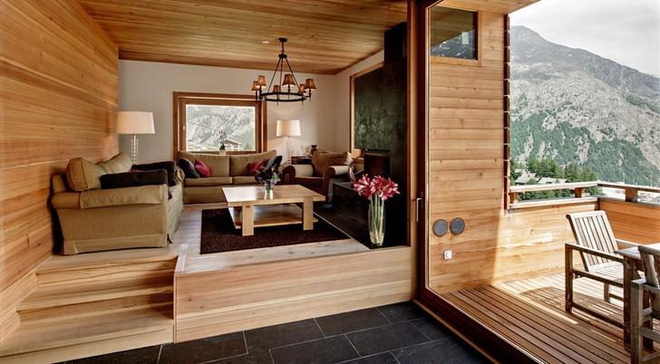 Мансардный этаж виллы с выходом на веранду оформлен в стиле шале. Цвет светлой древесины смотрится выгодно в сочетании с темно-коричневой половой плиткой.