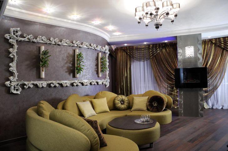Для оформления гостиной в стиле арт деко подобрана мягкая мебель горчичного цвета. Примечательная также лепнина на стене, которая напоминает витиеватую, фигурную рамку.