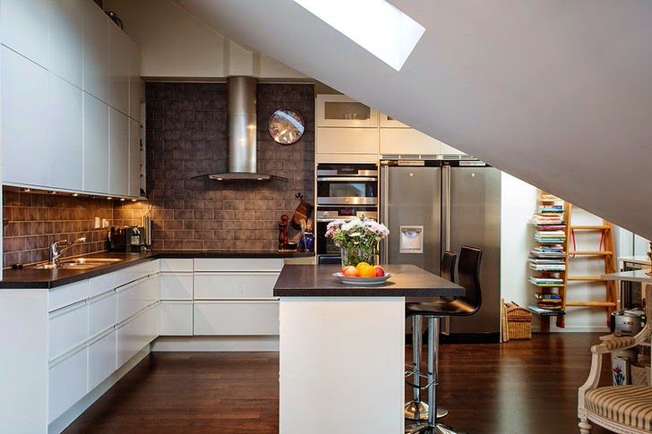 Кухня на мансардном этаже оформлена в скандинавском стиле. Белый кухонный гарнитур выгодно смотрится на фоне отделки стен из темного кирпича.