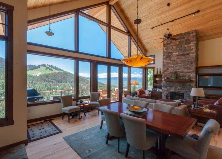 Дом в стиле шале с большими панорамными окнами обставлен в деревенском стиле. Гостиная-шале на мансардном этаже - глоток свежего воздуха после тяжелых рабочих дней.