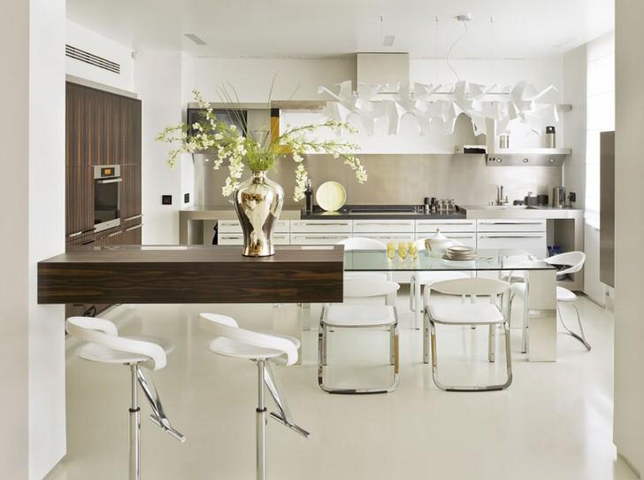 Просторная, светлая кухня в стиле модерн в квартире-студии. Дизайнер, чтобы отделить кухню от гостиной, использовал высокую барную стойку из темного дерева.