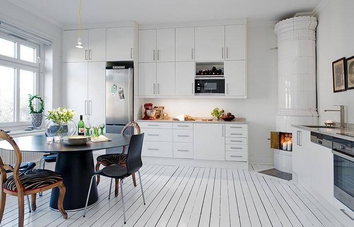 Изразцовый камин, обделанный белой керамической плиткой, органично вписывается в интерьер кухни в скандинавском стиле.