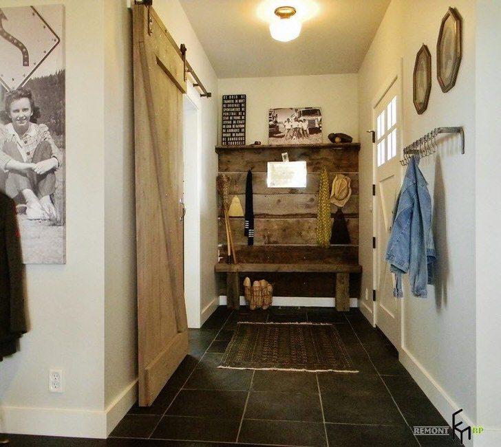 Прихожая в стиле лофт декорирована большим количеством деревянных элементов.