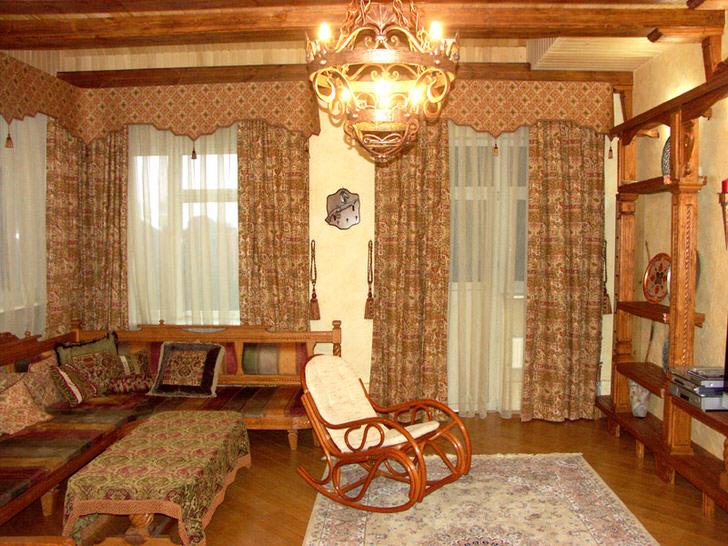 Жесткие ламбрекены использованы для оформления гостиной в загородном, охотничьем домике.
