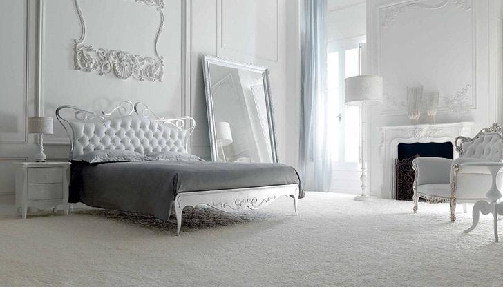 Стена в изголовье кровати украшена декоративной лепниной из гипса. Белоснежный интерьер примечателен огромным, широким зеркалом в простой, лаконичной раме.