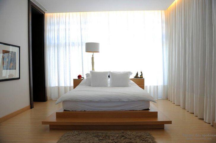 Кровать напоминает большую мягкую перину, которая расположилась на высоком подиуме из дерева. Занавески из мягкой, полупрозрачной, летучей ткани делают атмосферу в комнате романтичной и расслабляющей.