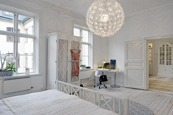 Просторная спальня в скандинавском стиле украшена массивной потолочной люстрой сферической формы. Цветы на окне освежают интерьер.