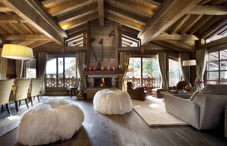 Взгляд притягивают меховые пуфики, которые делают обстановку в гостиной в стиле шале притягательной и чарующей.