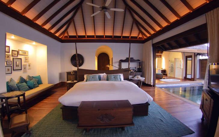 Мебель из массива дерева темного дерева смотрится роскошно и элегантно. Потолочная люстра подобрана в лучших традициях стиля.