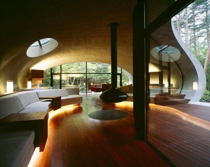 Интерьер дома в эко стиле украшен декоративным подвесным камином.