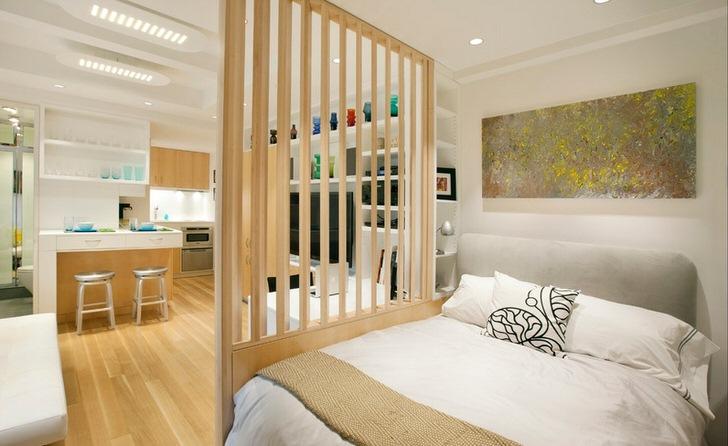 В квартире-студии спальная зона отделена декоративной перегородкой из дерева.
