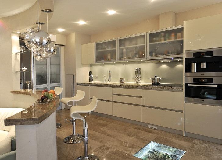 Кухня-рукав организованна практично и элегантно. По одну сторону расположился кухонный гарнитур, а по другую - барная стойка, используемая также в качестве кухонного стола.