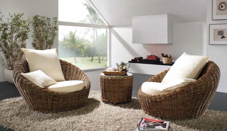 Плетеные объемные кресла с белыми мягкими подушками в комплекте с ковром с высоким ворсом станут лучшим украшением комнаты для гостей в эко стиле.