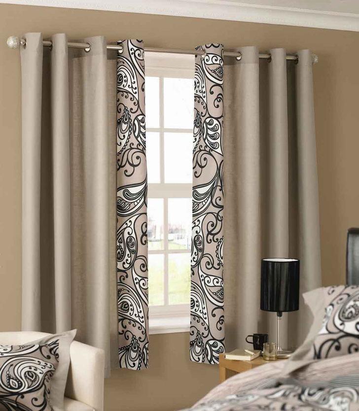 Стильные короткие шторы светло-пурпурного цвета повторяют узор, которым украшено постельное белье в спальне в стиле модерн.
