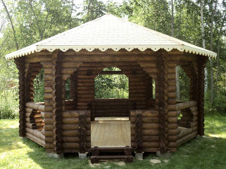 Беседка в стиле шале построена из состаренного сруба. Просторное строение станет изящным украшением любого двора.
